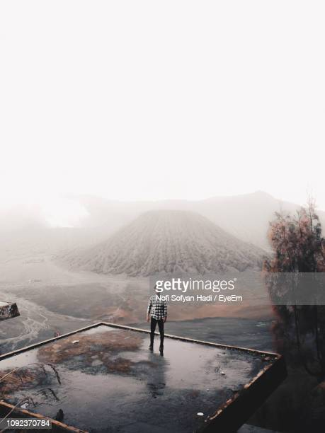 Full Length Of Man Standing Against Mountains And Sky During Foggy Weather