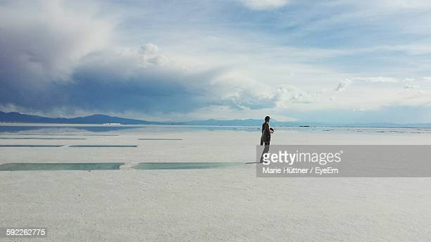Full Length Of Man Standing At Salinas Grandes Against Cloudy Sky