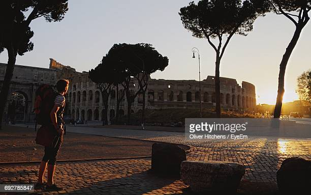 Full Length Of Man Standing By Coliseum During Sunset