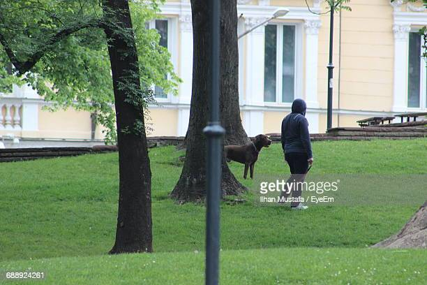 Full Length Of Man Standing By Dog At Park