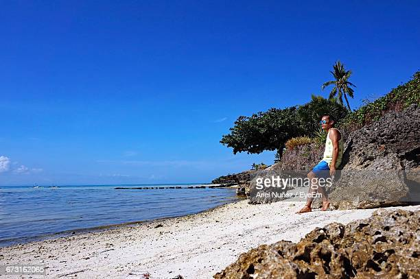 Full Length Of Man Standing By Rock At Beach Against Clear Blue Sky