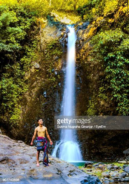 Full Length Of Man Standing By Waterfall In Forest