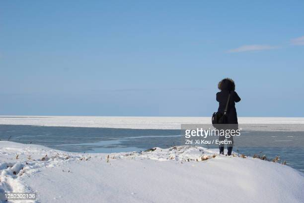 full length of man standing on beach - sea of okhotsk stock pictures, royalty-free photos & images