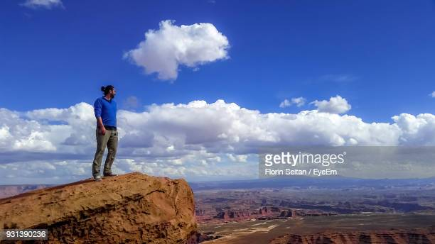 full length of man standing on cliff against sky - florin seitan stock pictures, royalty-free photos & images