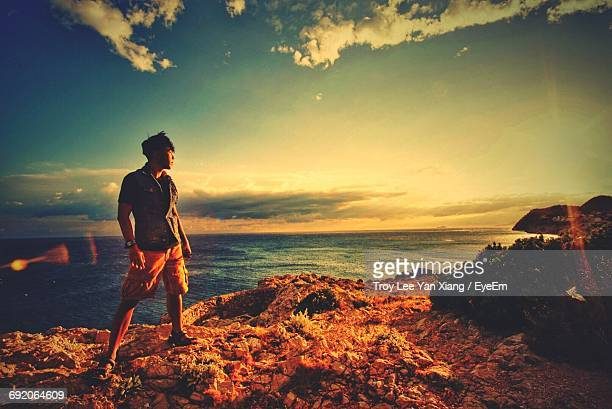 Full Length Of Man Standing On Cliff By Sea Against Sky During Sunset