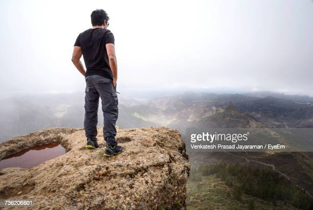Full Length Of Man Standing On Cliff While Looking At Mountains During Foggy Weather