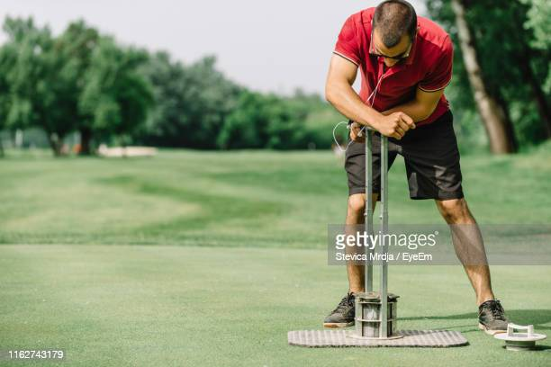 full length of man standing on golf course - ground staff stock pictures, royalty-free photos & images