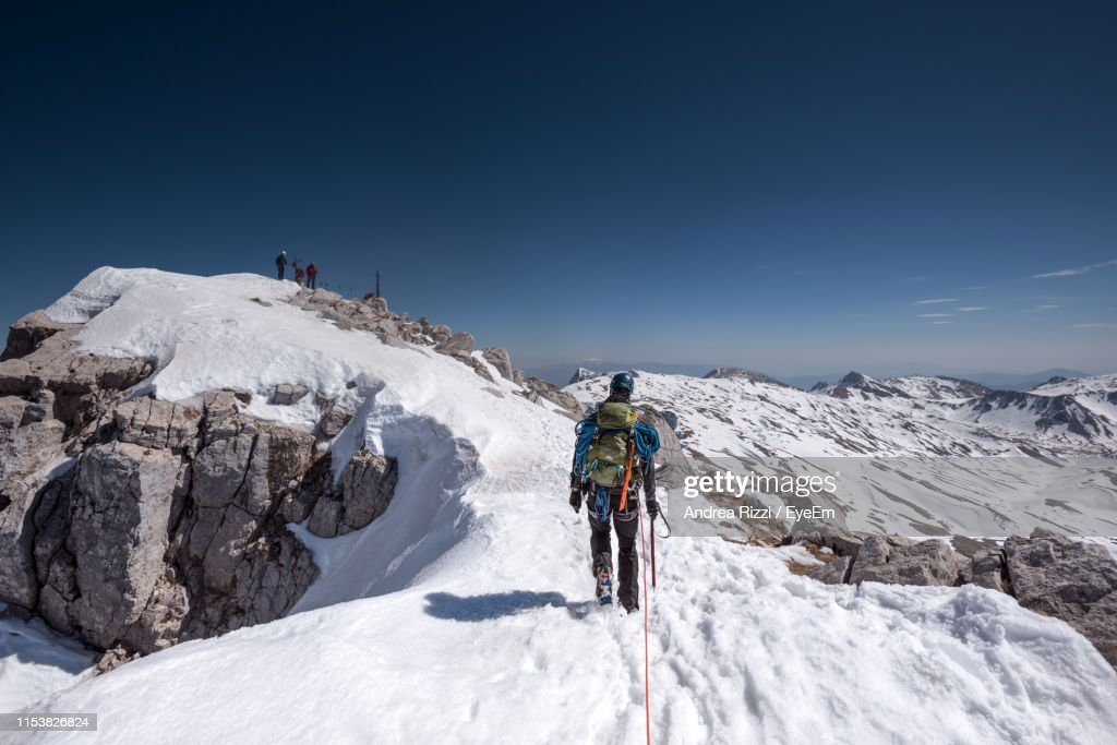 Full Length Of Man Standing On Mountain During Winter Against Sky : Foto stock