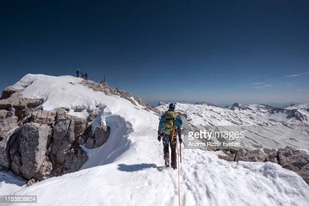 full length of man standing on mountain during winter against sky - andrea rizzi stock pictures, royalty-free photos & images