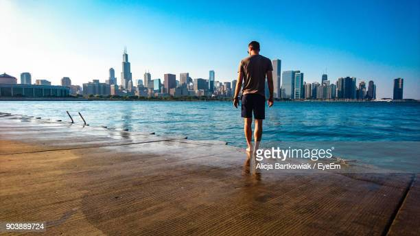 full length of man standing on promenade against blue sky in city - chicago illinois fotografías e imágenes de stock