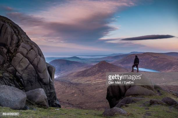 full length of man standing on rock against cloudy sky at dusk - belfast stock pictures, royalty-free photos & images