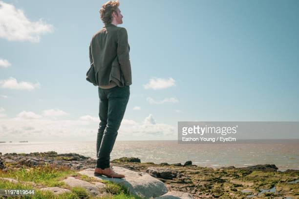 full length of man standing on rock against sky - standing stock pictures, royalty-free photos & images