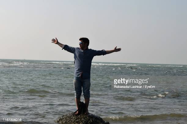 full length of man standing on rock at beach against sky - cox's bazaar stock pictures, royalty-free photos & images