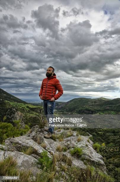 Full Length Of Man Standing On Rock At Mountain Against Cloudy Sky