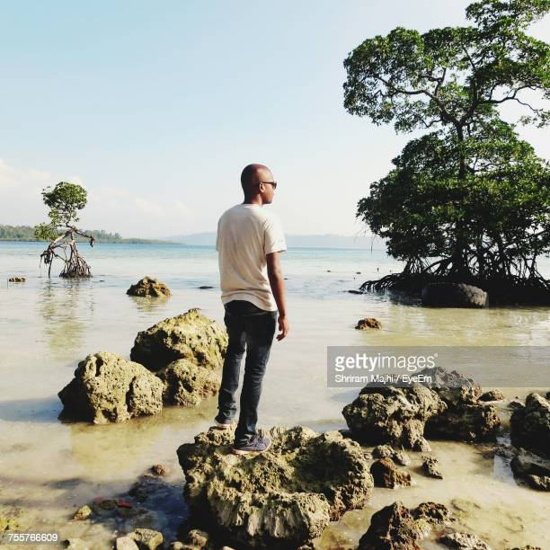 Full Length Of Man Standing On Rock In Sea Against Sky