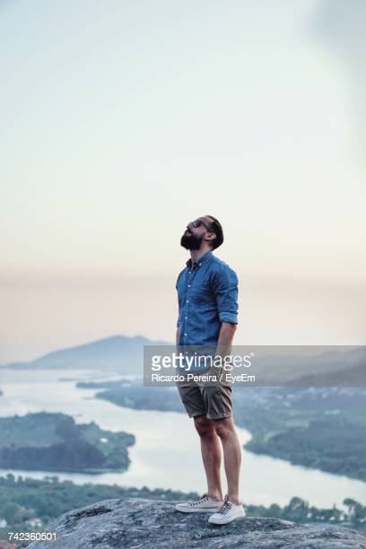 full length of man standing on rock - looking up stock pictures, royalty-free photos & images