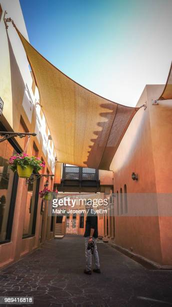 full length of man standing on street in town - qatar stock pictures, royalty-free photos & images
