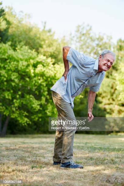 full length of man suffering from back pain while standing on field - tree man syndrome stock photos and pictures