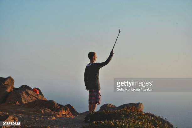 Full Length Of Man Taking Selfie While Standing On Mountain Against Sky
