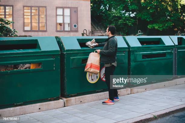 full length of man throwing garbage in can - garbage can stock photos and pictures