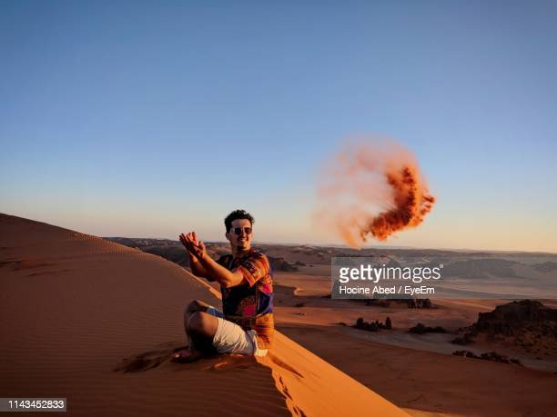 full length of man throwing sand while sitting on sand dune - algeria stock pictures, royalty-free photos & images