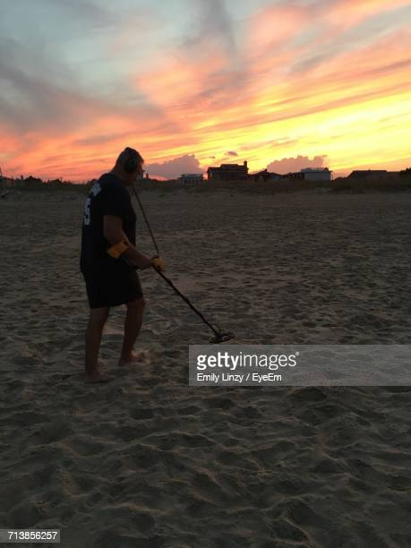 Full Length Of Man Using Metal Detector At Sandy Beach Against Sky During Sunset