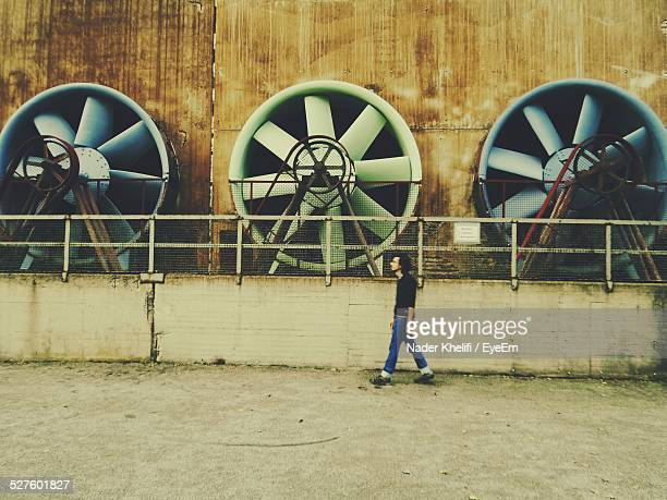 Full Length Of Man Walking Against Electric Fans On Industry