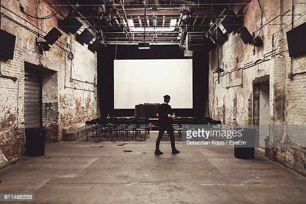Full Length Of Man Walking Against Projection Screen In Studio