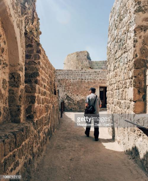 full length of man walking amidst old ruin - bahrain stock pictures, royalty-free photos & images