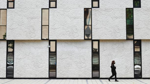 Full Length Of Man Walking On Footpath Against Building In City