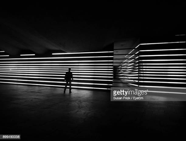 Full Length Of Man Walking On Illuminated Wall