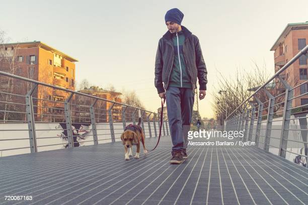 Full Length Of Man Walking With Dog On Footbridge In City