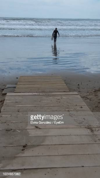 full length of man walking with surfboard on shore at beach against sky - castellon province stock pictures, royalty-free photos & images