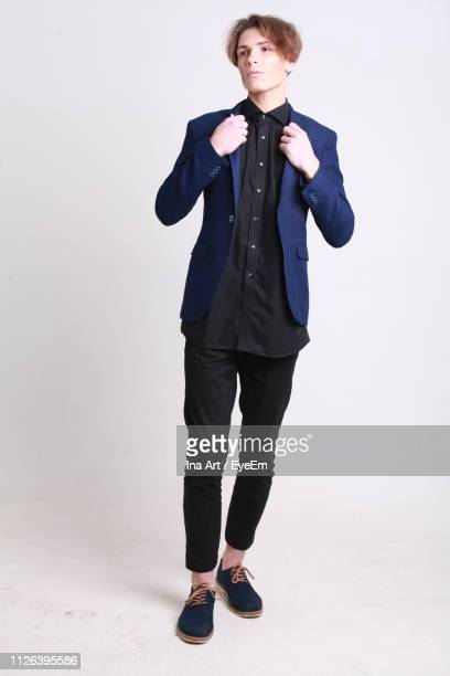 full length of man wearing suit while standing against white background - mannequin homme photos et images de collection