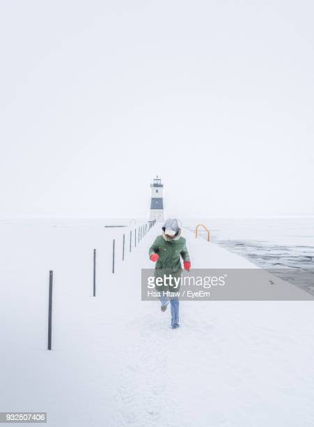 Full Length Of Man Wearing Walking Clothing While Running On Pier Against Lighthouse Against Clear Sky During Winter
