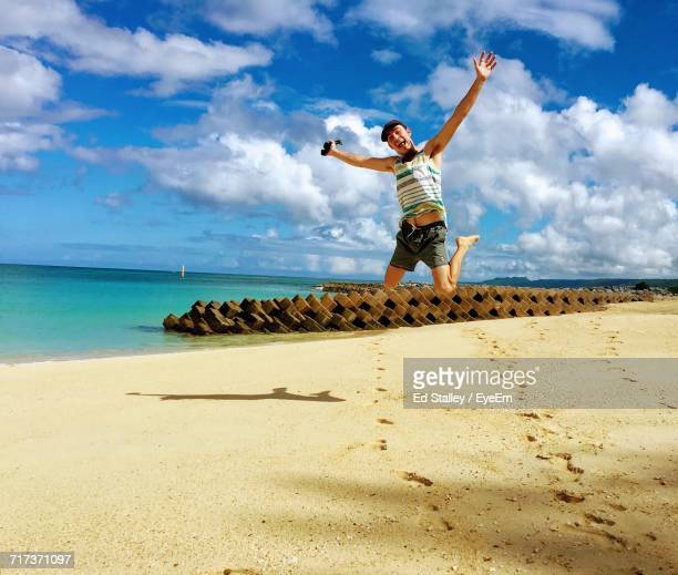 Full Length Of Man With Arms Outstretched Jumping At Beach Against Sky