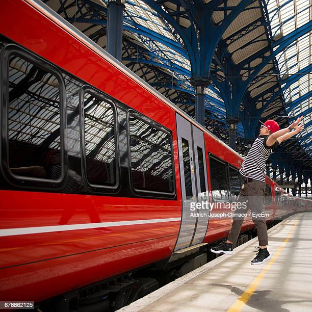 Full Length Of Man With Arms Outstretched Jumping By Red Train At Railroad Station