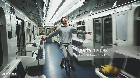 Full Length Of Man With Arms Outstretched Riding Unicycle In Train