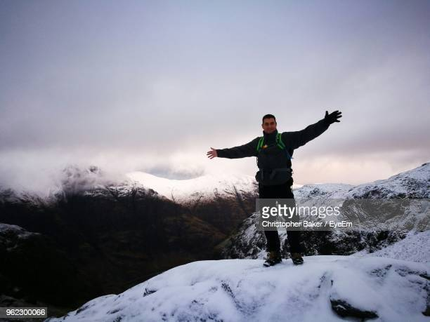 Full Length Of Man With Arms Outstretched Standing On Snow Against Sky