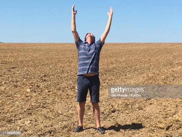 full length of man with arms raised standing on field - arms raised stock pictures, royalty-free photos & images