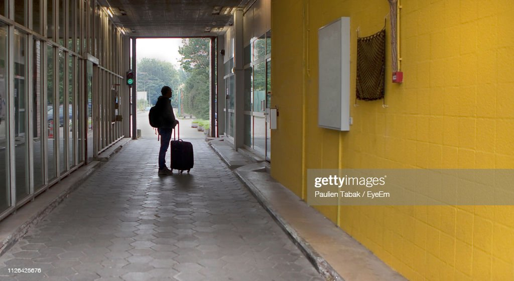 Full Length Of Man With Luggage Standing On Footpath By Buildings : Stockfoto