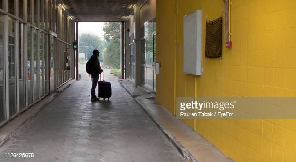 full length of man with luggage standing on footpath by buildings - paulien tabak stock pictures, royalty-free photos & images