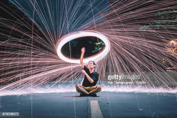 full length of man with wire wool sitting on road at night - brilliant stock photos and pictures