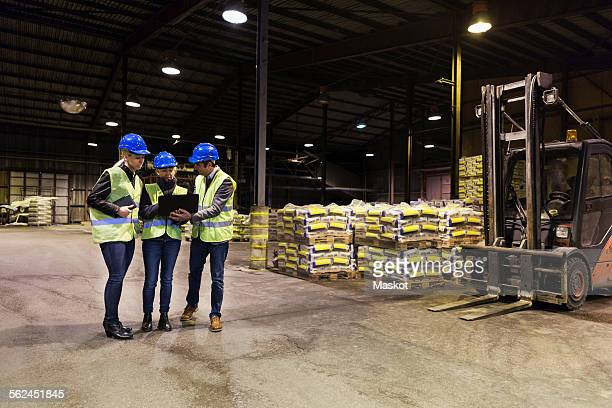Full length of manual workers using laptop in cement warehouse