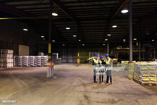 Full length of manual workers using technologies in cement warehouse