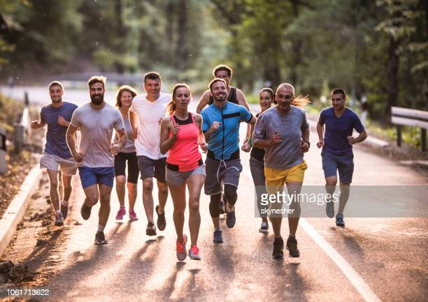 full length of marathon runners having a race through nature. - jogging stock pictures, royalty-free photos & images