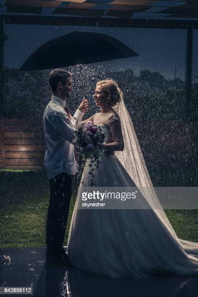 Full length of married couple standing on a rain with an umbrella.