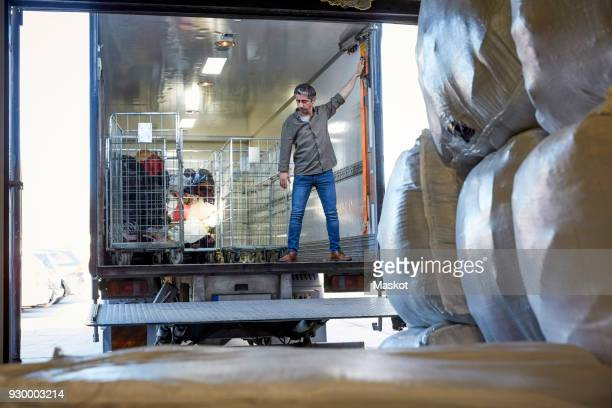 full length of mature male volunteer standing in semi-truck at warehouse - offloading stock pictures, royalty-free photos & images
