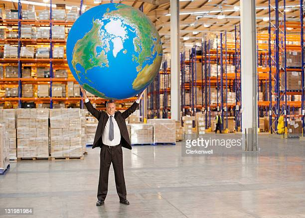 Full length of mature man holding aloft huge blue ball