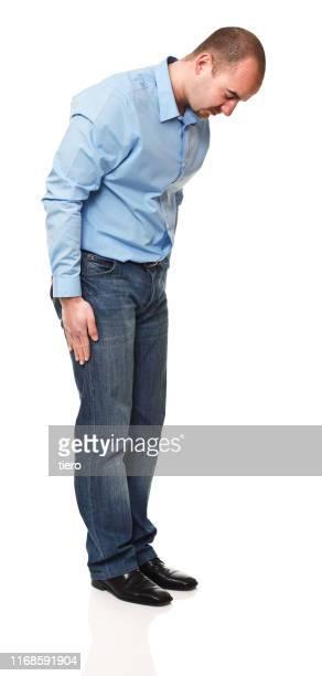 full length of mature man standing against white background - beugen oder biegen stock-fotos und bilder